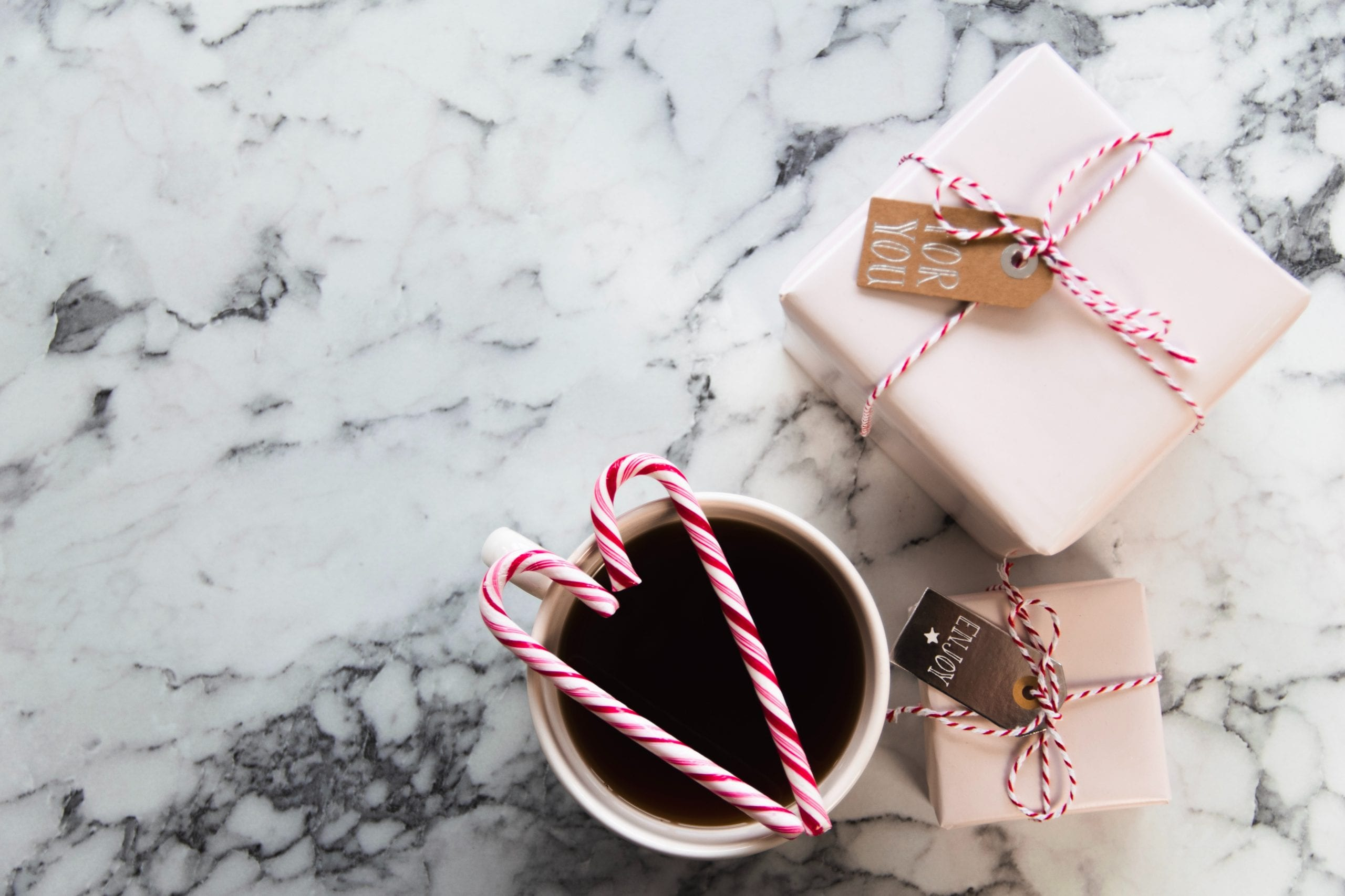 mug with coffee next to 2 white gift boxes & 2 sugar canes on the coffee mug